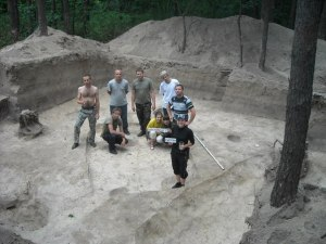 Nine team members posing for a photo after weeks of work at the Shestovitsja archaeological complex in Ukraine